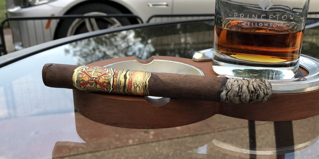Fuente OpusX Rosado Oscuro Oro Reserva D'Chateau Cigar on ashtray with bourbon glass